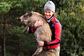 Eloi carries a baby of a wild pig.